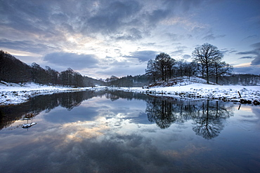 Winter view of River Brathay at dawn, under snow with reflections, near Elterwater Village, Ambleside, Lake District National Park, Cumbria, England, United Kingdom, Europe