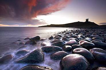 Dawn over Embleton Bay with basalt boulders in the foreground and the ruins of Dunstanburgh Castle in the background, near Alnwick, Northumberland, England, United Kingdom, Europe