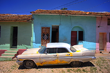 Classic American car parked on cobbled street outside brightly painted houses, Trinidad, Cuba, West Indies, Central America