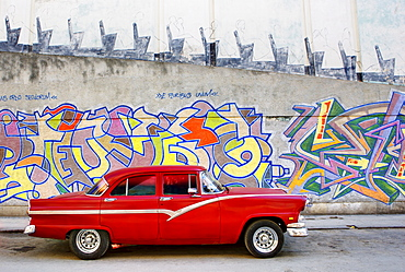 Classic red American car parked in front of grafitti covered wall, Havana, Cuba, West Indies, Central America