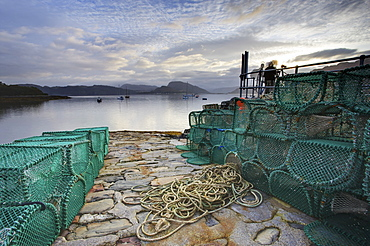 View out to sea from stone slipway at dawn, with lobster pots and ropes in foreground, Plokton, near Kyle of Lochalsh, Highland, Scotland, United Kingdom, Europe