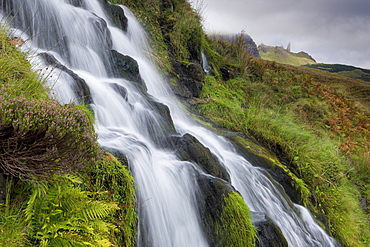 Waterfall cascading down grassy slope with Old Man of Storr in background, near Portree, Isle of Skye, Highland, Scotland, United Kingdom, Europe