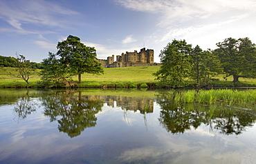 Alnwick Castle reflecting in River Aln, Alnwick, Northumberland, England, United Kingdom, Europe