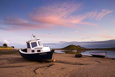 Fishing boat on the Aln Estuary at twilight, low tide, Alnmouth, near Alnwick, Northumberland, England, United Kingdom, Europe