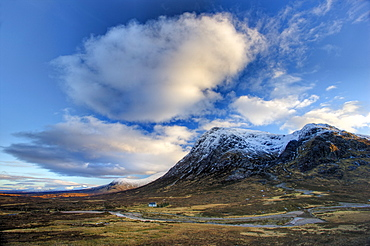 Winter view of Rannoch Moor showing lone whitewashed cottage on the bank of a river, dwarfed by snow-covered mountains, and dramatic evening sky, Rannoch Moor, near Fort William, Highland, Scotland, United Kingdom, Europe