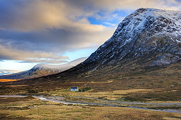 Winter view of Rannoch Moor showing lone whitewashed cottage on the bank of a river, dwarfed by snow-covered mountains, Rannoch Moor, near Fort William, Highland, Scotland, United Kingdom, Europe