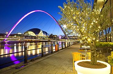 View along Newcastle Quayside at night showing the River Tyne, the floodlit Gateshead Millennium Bridge and the Sage Gateshead, Newcastle-upon-Tyne, Tyne and Wear, England, United Kingdom, Europe