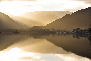 Morning sunlight bursting through clouds over fells with reflections in Lake Ullswater, near Glenridding Village, Lake District National Park, Cumbria, England, United Kingdom, Europe