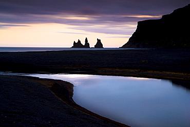 Twilight view towards rock stacks at Reynisdrangar off the coast at Vik, South Iceland, Iceland, Polar Regions