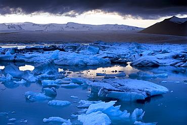 Blue icebergs floating on the Jokulsarlon glacial lagoon at sunset, South Iceland, Iceland, Polar Regions