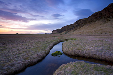 Stream meandering into the distance and reflecting colours in the twilight sky, near Hella, South Iceland, Iceland, Polar Regions