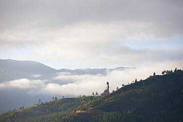 Misty early morning view of giant golden Buddha being constructed on a forested hillside outside Thimpu, Bhutan, Asia