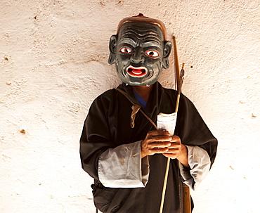 Monk dressed as a clown and wearing carved wooden mask collecting money from spectators at the Wangdue Phodrang Tsechu, Wangdue Phodrang Dzong, Wangdue Phodrang (Wangdi), Bhutan, Asia