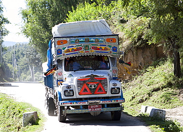 Colourfully decorated truck driving through a village in the Bumthang Valley, Bhutan, Asia