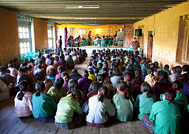Pupils and teachers in the main hall of their school taking part in a spelling competition, Ura Village, Ura Valley, Bumthang, Bhutan, Asia