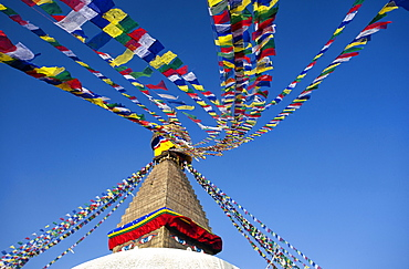 Bodhnath Stupa (Boudhanth) (Boudha), one of the holiest Buddhist sites in Kathmandu, UNESCO World Heritage Site, with colourful prayer flags against clear blue sky, Kathmandu, Nepal, Asia