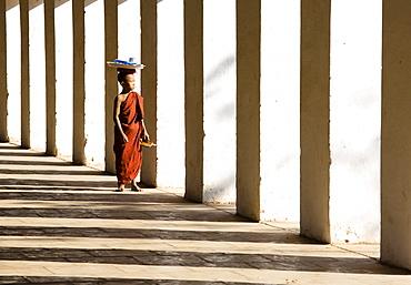Novice Buddhist monk standing in the shadows of columns at Shwezigon Paya, Nyaung U, Bagan, Myanmar (Burma), Asia
