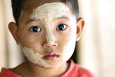Young Burmese child with Thanakha traditional face painting, Yangon (Rangoon), Myanmar (Burma), Asia