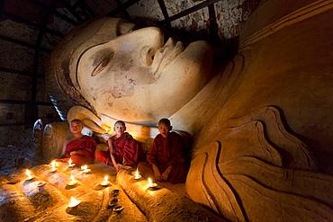 Three novice Buddhist monks sitting by a large reclining Buddha in the light of candles, near Shwesandaw Paya, Bagan, Myanmar (Burma), Asia