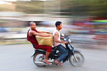 Panned and blurred shot creating a sense of movement, Buddhist monk riding pillion and carrying vegetables on the back of a moped, Mandalay, Myanmar (Burma), Asia
