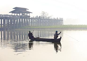 Fisherman on Taungthaman Lake in mist at dawn with U Bein Bridge, the world's longest teak foot bridge spanning 1300 yards, Amarapura, near Mandalay, Myanmar (Burma), Asia