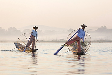Intha 'leg rowing' fishermen at dawn on Inle Lake who row traditional wooden boats using their leg and fish using nets stretched over conical bamboo frames, Inle Lake, Myanmar (Burma), Southeast Asia