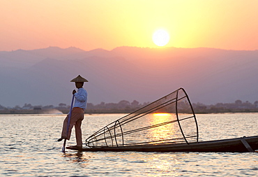 Intha leg rowing fishermen at sunset on Inle Lake who row traditional wooden boats using their leg and fish using nets stretched over conical bamboo frames, Inle Lake, Shan State, Myanmar (Burma), Asia