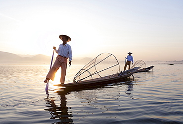 Intha leg rowing fishermen at dawn on Inle Lake who row traditional wooden boats using their leg and fish using nets stretched over conical bamboo frames, Inle Lake, Shan State, Myanmar (Burma), Asia