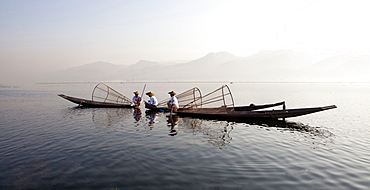 Intha leg rowing fishermen on Inle Lake who row traditional wooden boats using their leg and fish using nets stretched over conical bamboo frames, Inle Lake, Shan State, Myanmar (Burma), Asia