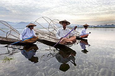 Intha leg rowing fishermen on Inle Lake who row traditional wooden boats using their leg and fish using nets stretched over conical bamboo frames, Inle Lake,Shan State, Myanmar (Burma), Asia