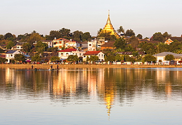 View of Kengtung (Kyaingtong) looking across Naung Tung Lake towards the town and gilded stupa of Wat Jong Kham bathed in evening light, Kengtung, Shan State, Myanmar (Burma), Asia
