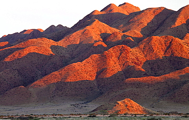 Sandstone mountains lit by the last rays of light from the setting sun, near Sesriem, Namib Desert, Namib Naukluft Park, Namibia, Africa