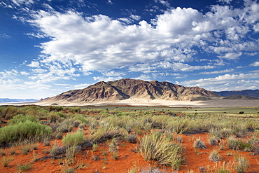 View across magnificent landscape of orange sand dunes and sandstones mountains at Wolwedans, part of the Namib Rand game reserve, Namib Naukluft Park, Namibia, Africa