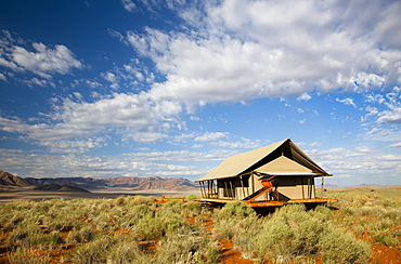 One of the luxury tents set in a magnificent landscape of orange sand dunes and sandstone mountains at Wolwedans Dune Camp in the Namib Rand game reserve, Namib Naukluft Park, Namibia, Africa