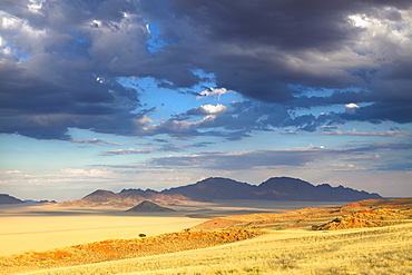 View at dusk over the magnificent desert and mountainous landscape of the Namib Rand game reserve, Namib Naukluft Park, Namibia, Africa