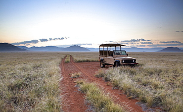 Land rover game vehicle parked by sand road at sunrise, Namib Rand game reserve, Namib Naukluft Park, Namibia, Africa
