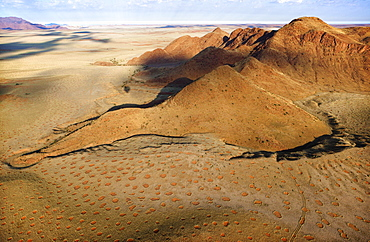Aerial view from hot air balloon over magnificent desert landscape of sand dunes, mountains and Fairy Circles, Namib Rand game reserve Namib Naukluft Park, Namibia, Africa