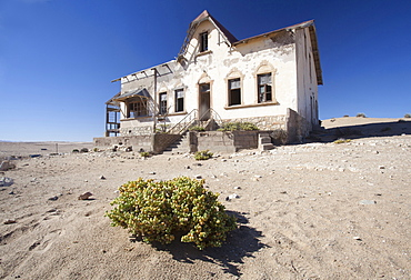 House slowly being reclaimed by the desert in the abandoned former German diamond mining town of Kolmanskop on the edge of the Namib Desert, Forbidden Diamond Area near Luderitz, Namibia, Africa