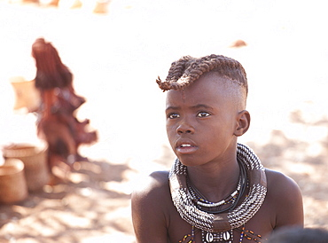 Young Himba boy with plaited hair wearing traditional jewellery around his neck, Kunene Region (formerly Kaokoland) in the far north of Namibia, Africa