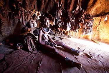 Young Himba woman inside a traditional mud dwelling hut wearing traditional dress and jewellery and with her skin covered in Otjize, a mixture of butterfat and ochre, Kunene Region, formerly Kaokoland, Namibia, Africa