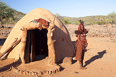 Young Himba woman standing outside her traditional mud-covered dwelling in a Himba village in the Kunene Region (formerly Kaokoland) in the far north of Namibia