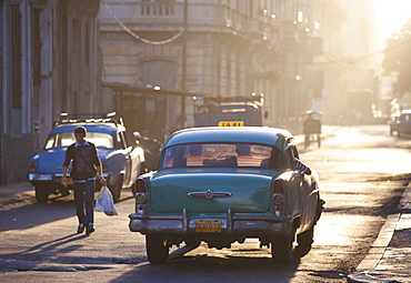 Vintage American car taxi on Avenue Colon during morning rush hour soon after sunrise, Havana Centro, Cuba, West Indies, Central America