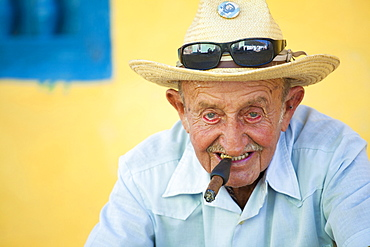 Portrait of old man wearing straw hat and smoking cigar, posing against a yellow wall for tourist pesos, Trinidad, Cuba, West Indies, Central America