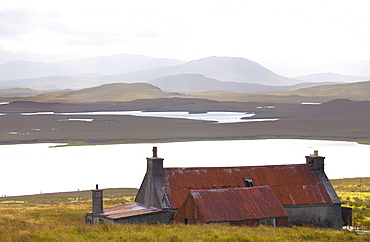 Farmhouse with red iron roof overlooking lochs and mountains off the A858 south of Carloway, Isle of Lewis, Outer Hebrides, Scotland, United Kingdom, Europe