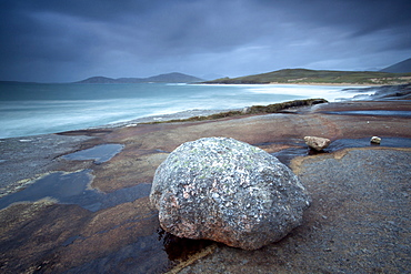 Large erratic boulder on the rocky coastline at Scarista with a view over the sand towards the hills of Taransay, Scarista, Isle of Harris, Outer Hebrides, Scotland, United Kingdom, Europe