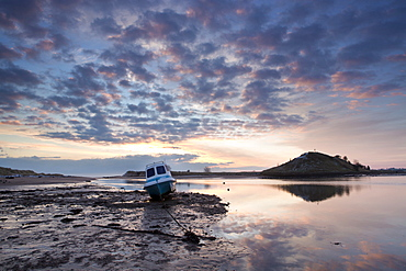 Winter sunrise on the Aln Estuary with a single boat moored on the mud flats, looking towards Church Hill reflecting in the calm water, Alnmouth, near Alnwick, Northumberland, England, United Kingdom, Europe