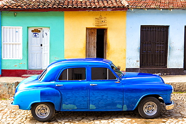Bright blue vintage American car parked in front of colourful painted colonial houses, Trinidad, UNESCO World Heritage Site, Cuba, West Indies, Central America