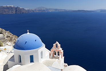 Classic view over the Caldera showing blue domed church and pink belltower, Oia, Santorini, Greek Islands, Greece, Europe