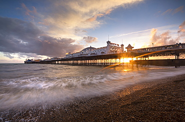 Brighton Pier at sunset with dramatic sky and waves washing up the beach, Brighton, East Sussex, England, United Kingdom, Europe