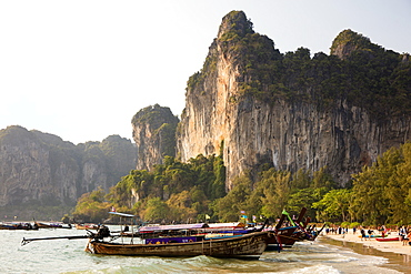 Traditional Longtail boats moored by Railay Beach with limestone cliffs in the background, Ao Nang, Krabi, Thailand, Southeast Asia, Asia